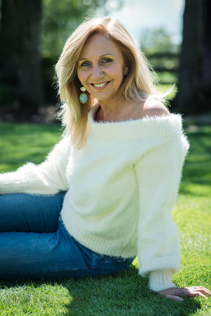 Hilary Robinson sitting on the grass, smiling to the camera.