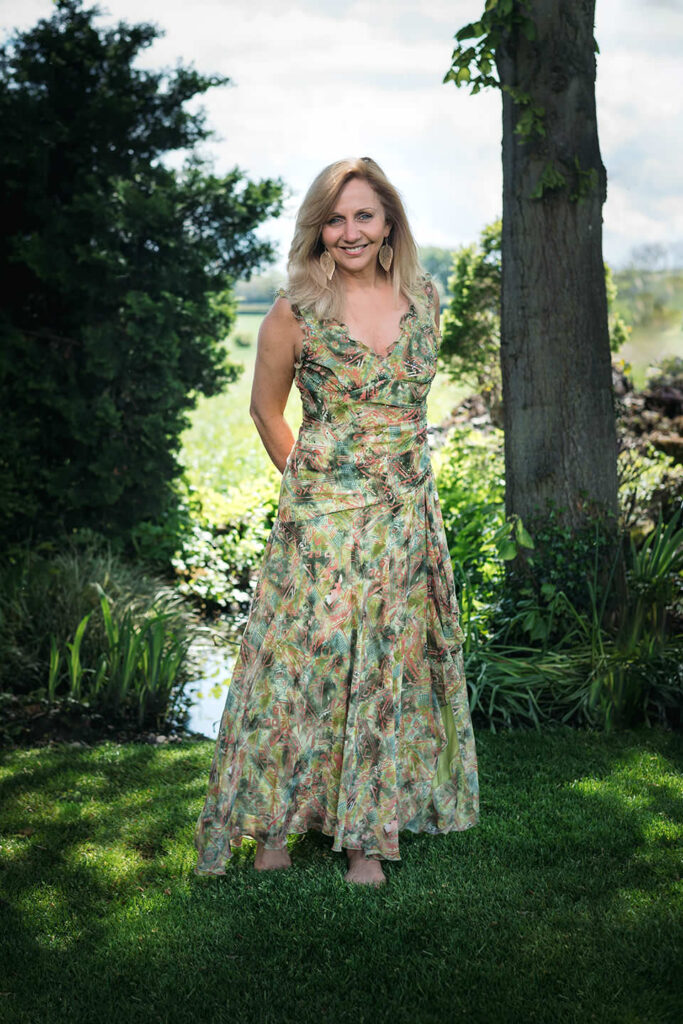 Hilary Robinson wearing a flowery dress, standing in the garden.