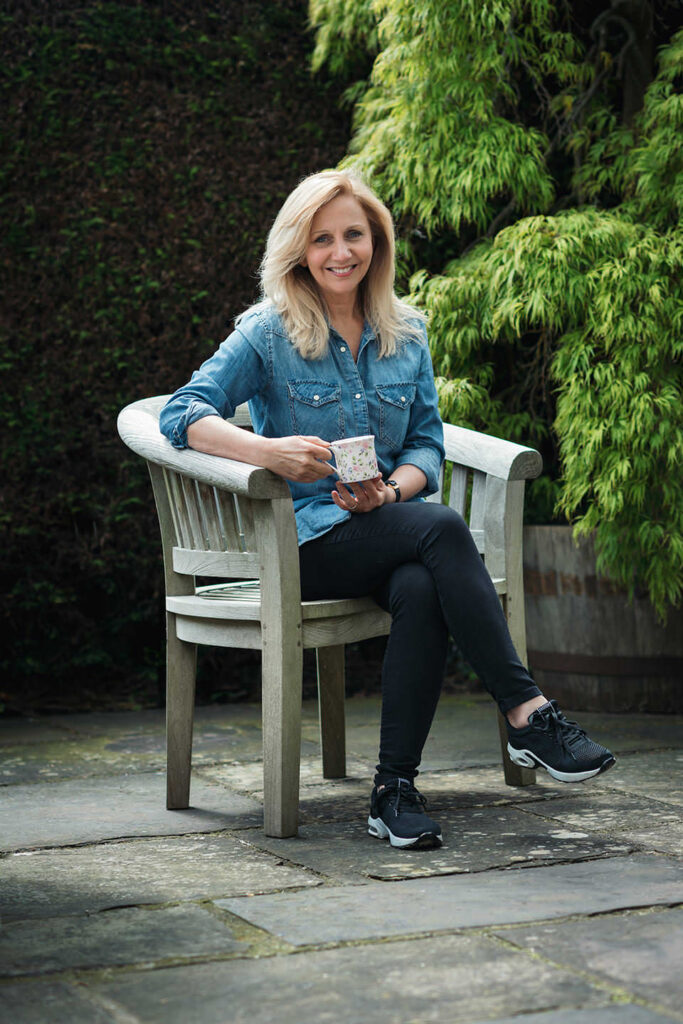 Hilary Robinson sitting on a wooden garden chair, holding a cup of tea.