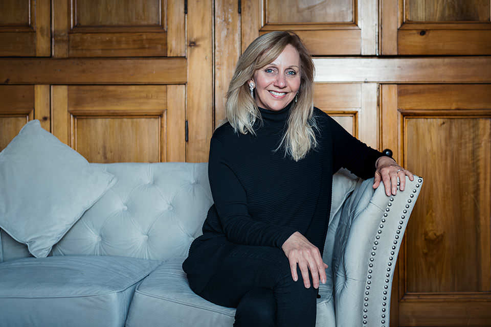 Hilary Robinson sitting on a sofa in a panelled room.