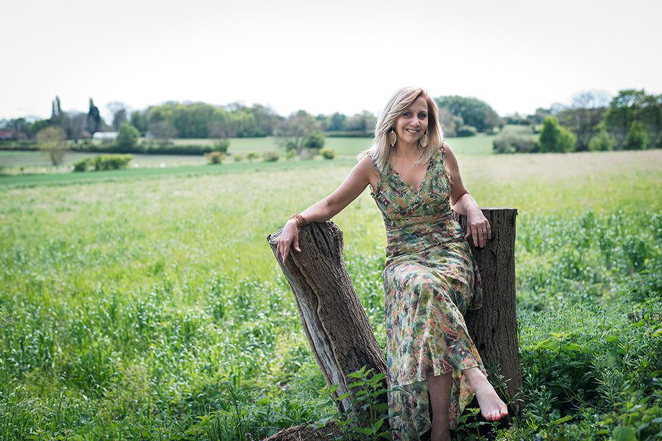 Hilary Robinson wearing a flowery dress sitting on a tree stump in a meadow.
